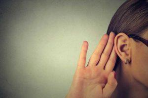 femme qui met main derrière oreille pour écouter