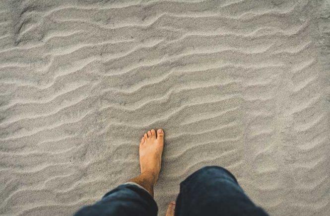 un homme pieds nus dans le sable