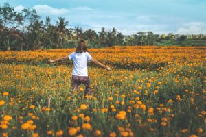 femme qui marche avec bras ouverts dans champ fleurs