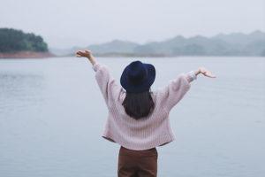 femme qui lèvent les bras face à la mer