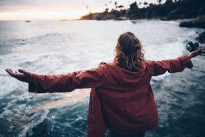 femme qui ouvre les bras face à la mer