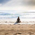 femme qui médite sur une plage face à la mer