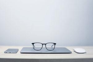 bureau avec téléphone ordinateur et lunettes