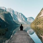 homme assis qui regarde lac et montagnes